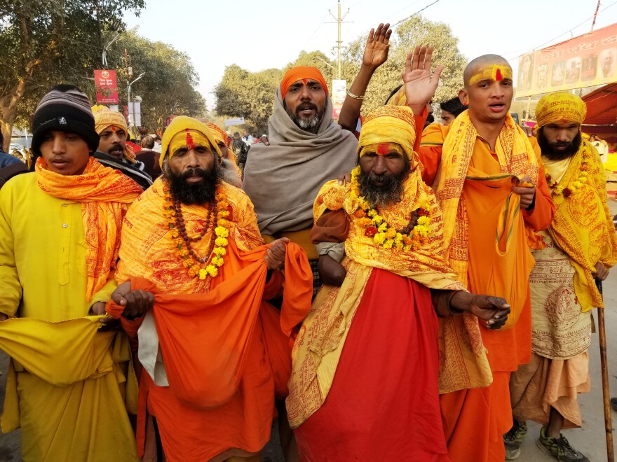 Hindu priests draped in orange sarongs and garlands of marigolds are among the pilgrims.