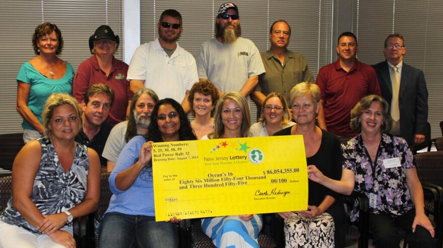 The winners of the Aug. 7 Powerball jackpot pose with a check for their share of the $448 million grand prize.
