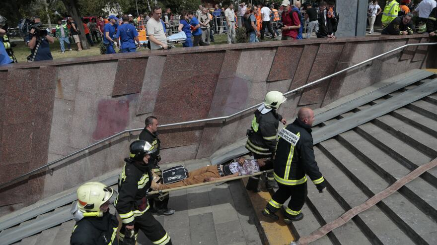 Firefighters carry an injured man out from a subway station after a rush-hour subway train derailment in Moscow on Tuesday.