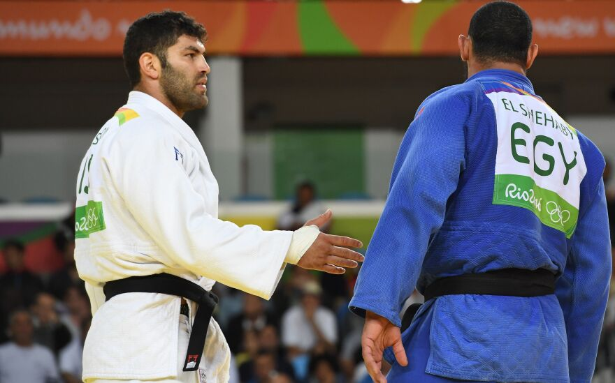 Israel's Or Sasson (left) ties to shake hands with Egypt's Islam El Shehaby during their men's 100kg judo contest match on Aug. 12.