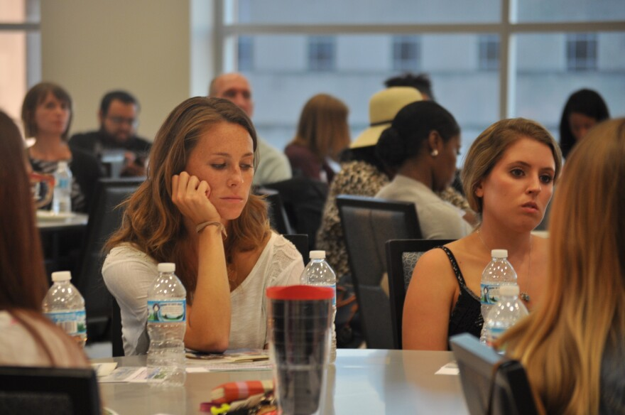 """Attendees at the St. Louis University Law School listen to a recording of """"Mindstorm,"""" a simulation of audio hallucinations sometimes experienced by people living with schizophrenia."""