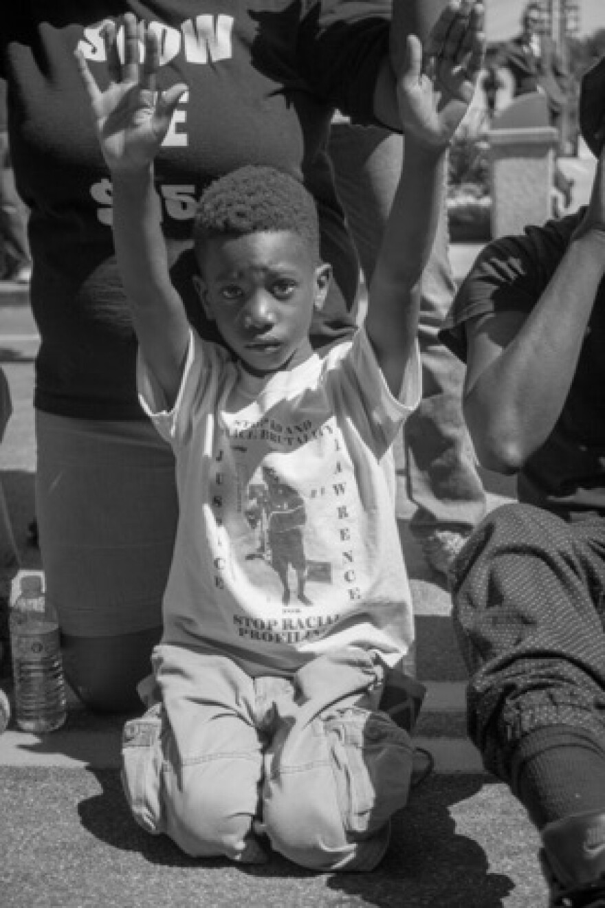 Child displays Hands Up pose common during Ferguson-related protests