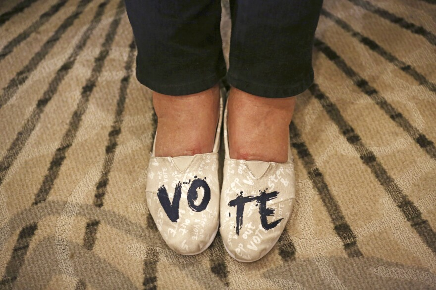 "Anne Mullen, of Dallas, wears shoes with ""VOTE"" written on them during an election night party in Dallas in 2018."