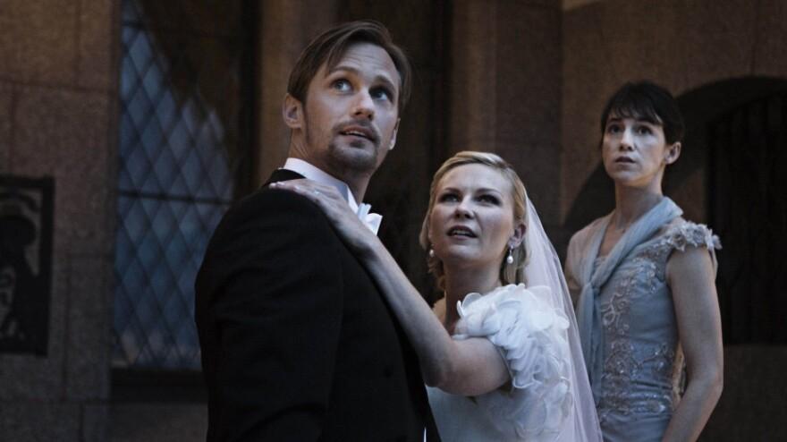 A bride (Kirsten Dunst, with Alexander Skarsgard and Charlotte Gainsbourg) battles depression — and the possible end of the world — in <em>Melancholia.</em>