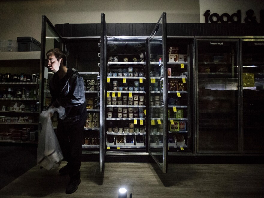 James Quinn throws out ice cream from freezers at a CVS during an intentional blackout in Sonoma, Calif., on Oct. 9.