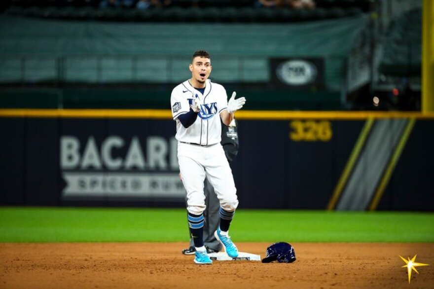 Tampa Bay Rays player claps his hands while standing on second base.