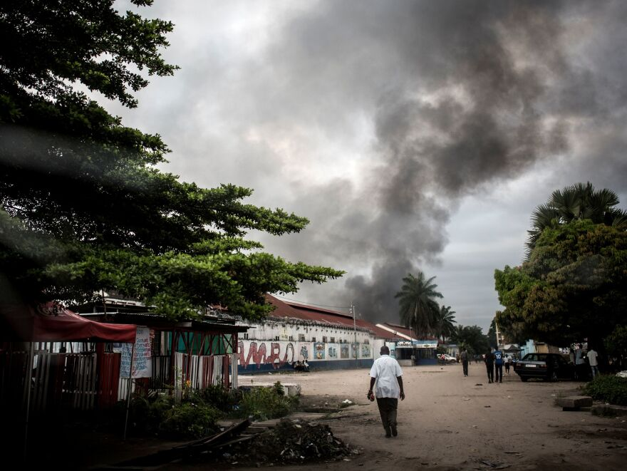 A man walks toward the smoke rising from a fire at the Independent National Electoral Commission's warehouse in Kinshasa on Thursday, 10 days ahead of the presidential election.