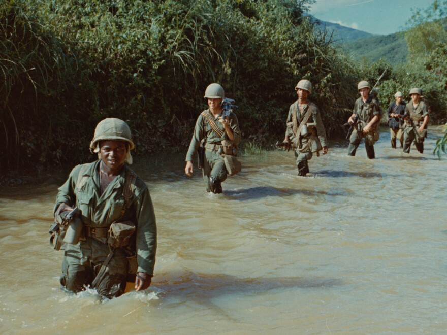 American soldiers advance through a rice paddy during the Vietnam War.