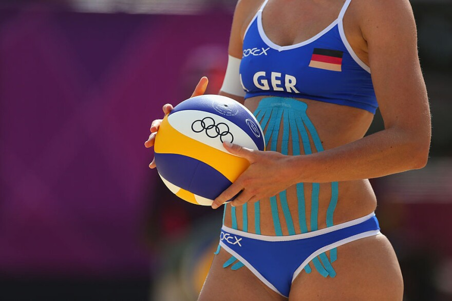 Katrin Holtwick, of Germany's 2012 beach volleyball team, prepares to serve at the 2012 Olympics in London. Holtwick is bedecked in a stretchy cotton tape widely used by some athletes because they think it supports sore muscles, or improves range of motion.