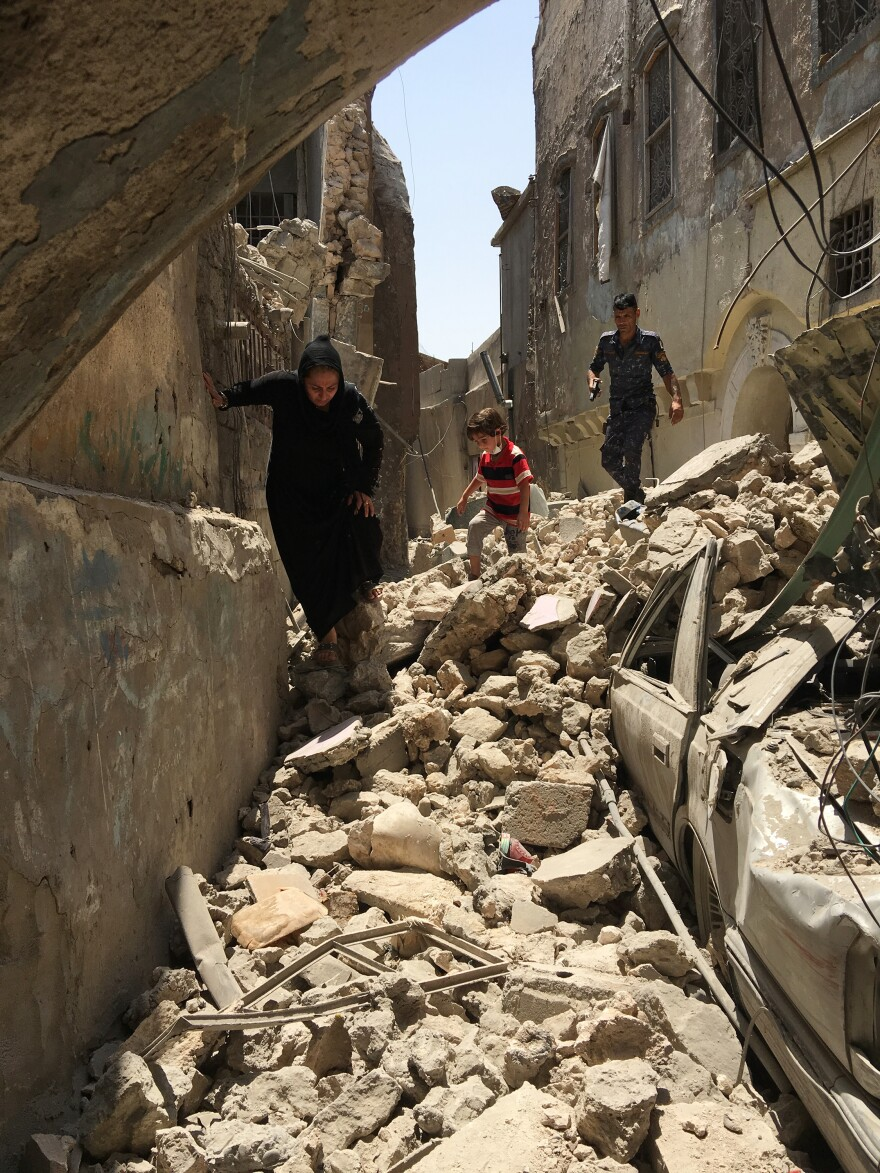 People climb through destroyed streets in Mosul. Many were crushed under the rubble of collapsed houses hit by mortars and air strikes — trapped when ISIS wouldn't let them leave and Iraqi forces told them to stay indoors.
