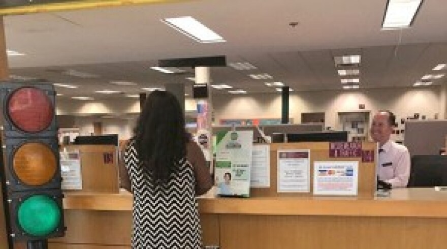 Woman stands at the front of the Pinellas County Clerk front office counter.
