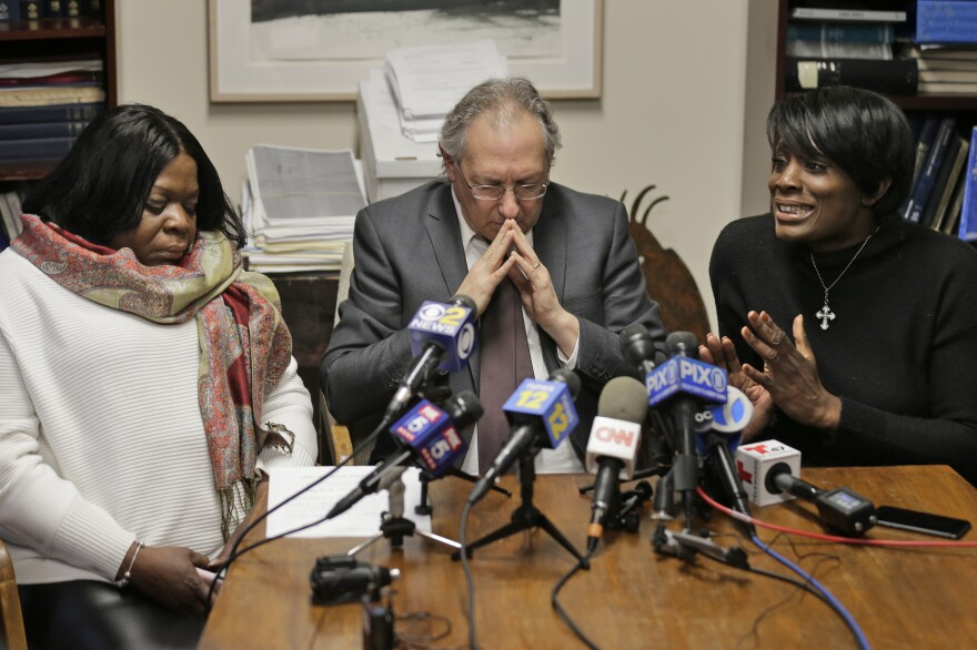 Kim Thomas (left), mother of Grafton Thomas, the man accused of stabbing five people at a Hanukkah celebration, and attorney Michael Sussman (center) listen as the Rev. Wendy Paige speaks about Grafton Thomas at a news conference in Goshen, N.Y., on Monday.
