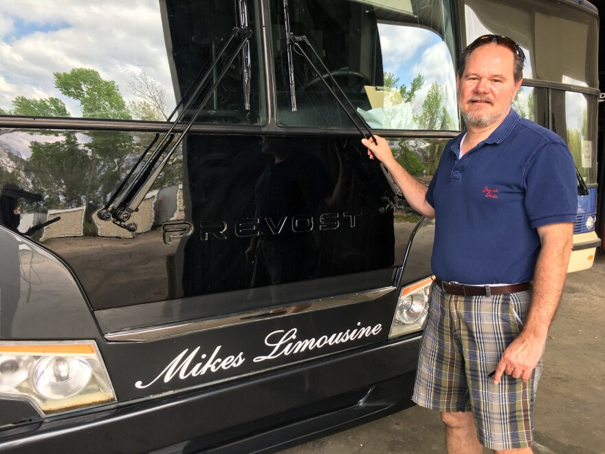 Ted Redig, General Manager for Mikes Limousine Service, stands next to one of the company's charter buses.