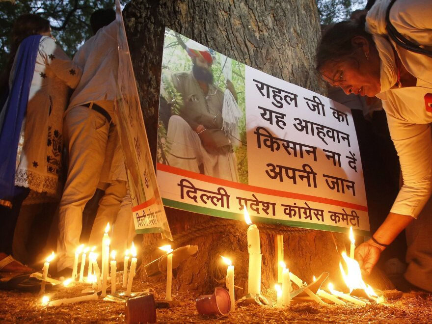 An Indian National Congress party worker on Thursday pays tribute to Gajendra Singh, a farmer who committed suicide during a candlelight vigil in New Delhi the previous day.