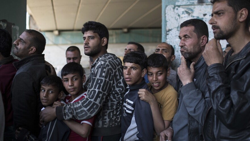 Iraqis line up for food distribution on Wednesday in West Mosul.