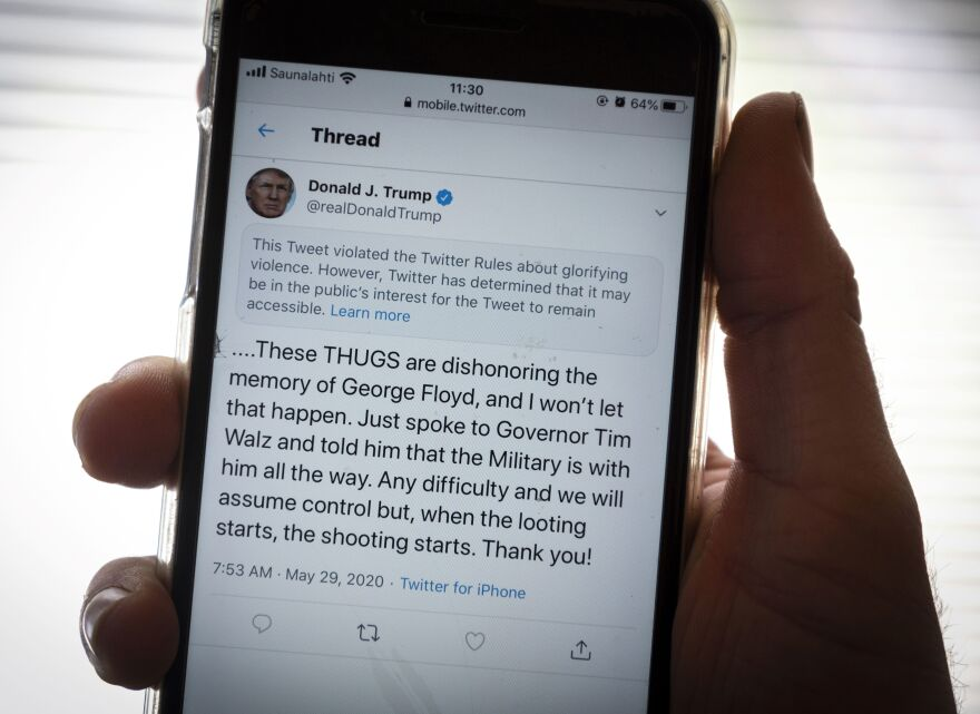 """President Trump's Twitter page is displayed on a mobile phone. The social media company flagged one of his tweets about Minneapolis as """"glorifying violence"""" and hid it from public view unless a user clicks on it."""