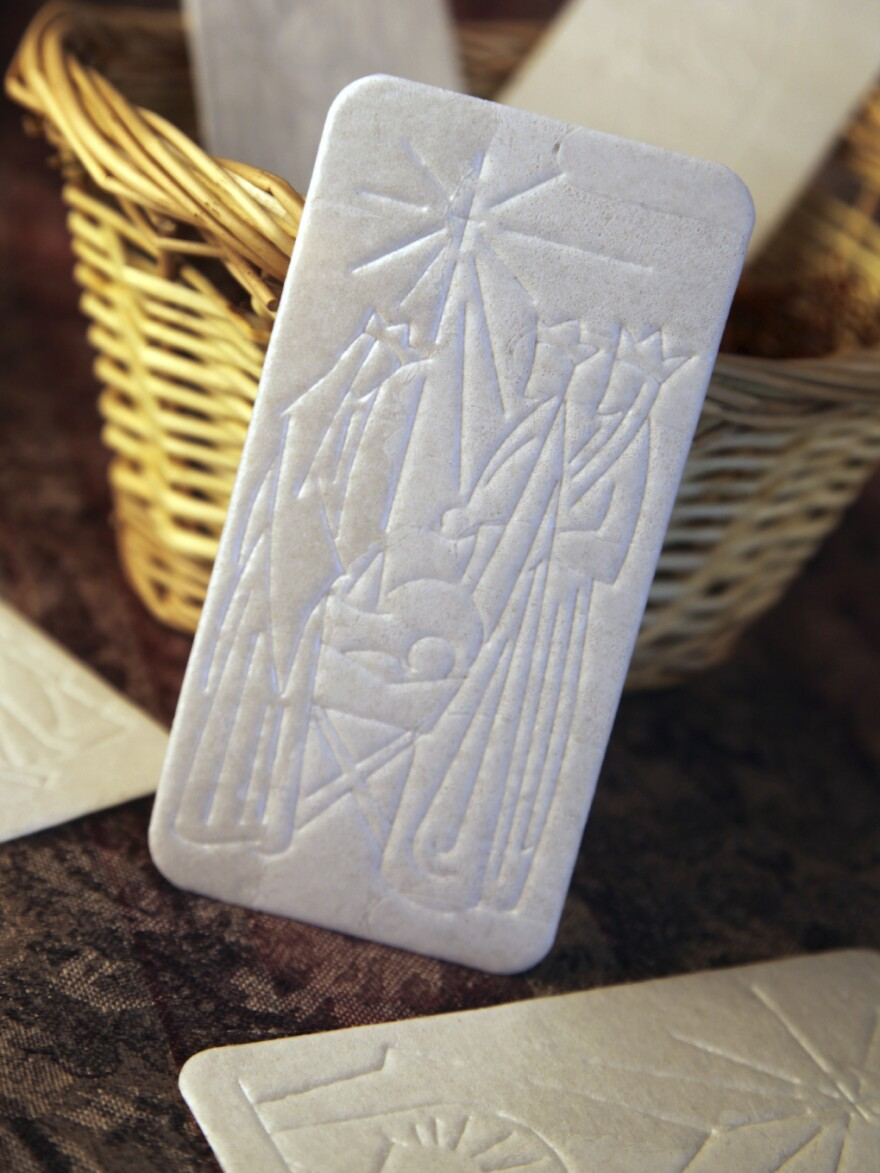 The <em>oplatek</em>, embossed with a Christmas scene, is shared among family members before Christmas Eve dinner.