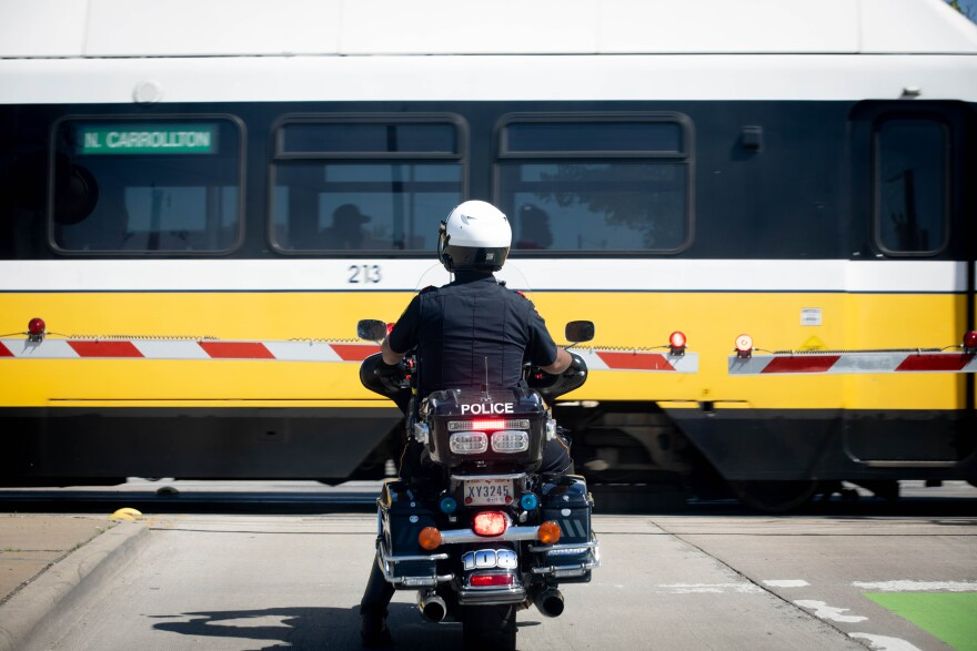 A uniformed Dallas police officer on a motorcycle waits at a train crossing for a DART train to pass.