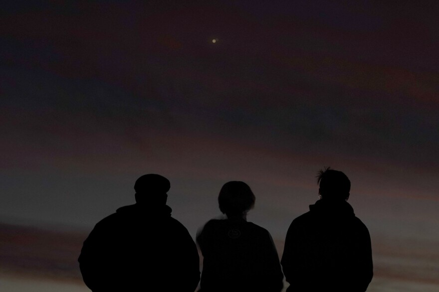 People watch the alignment of Saturn and Jupiter on Monday in Edgerton, Kan. The two planets are in their closest observable alignment since 1226.