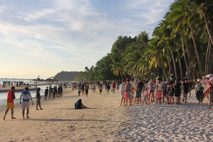 Tourists walk along a beach in Malay town, on the Philippine island Boracay, last week. President Duterte's decision to close Boracay has rocked the island. The Philippines is set to deploy hundreds of riot police to keep travelers out and head off potential protests before its six-month closure to tourists.