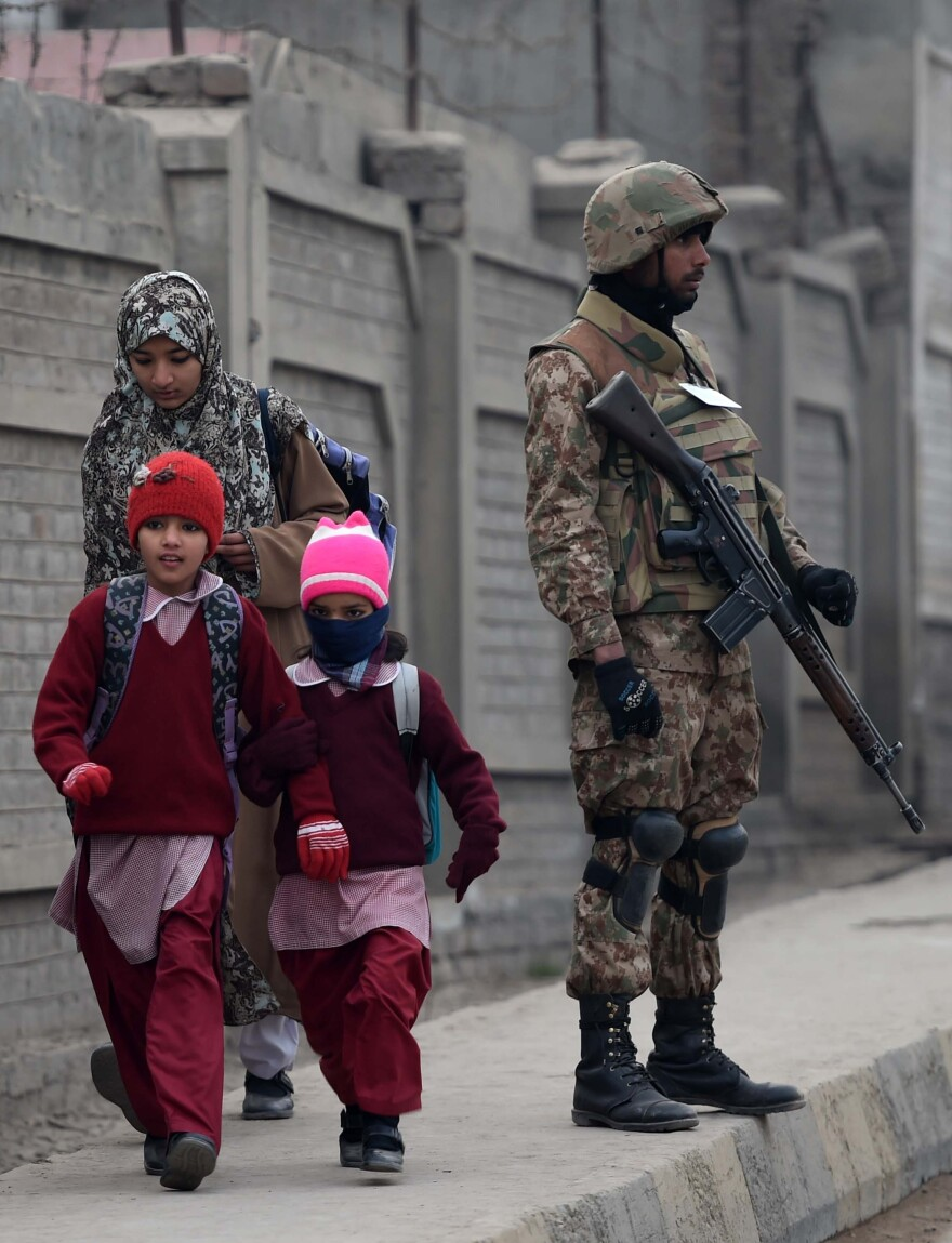 A Pakistani soldier stands guard on a street as children walk to school in Peshawar on Monday.
