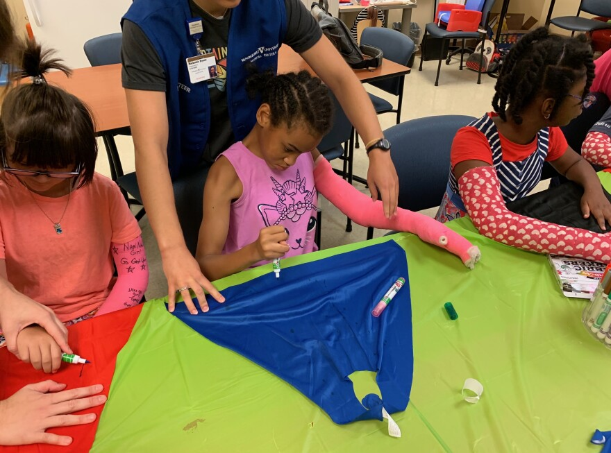 "At Nashville's ""High Five"" camp, 12-year-old Priceless Garinger (center), whose right side has been weakened by cerebral palsy, wears a full-length, bright pink cast on her left arm — though that arm's strong and healthy. By using her weaker right arm and hand to decorate a cape, she hopes to gain a stronger grip and fine motor control."
