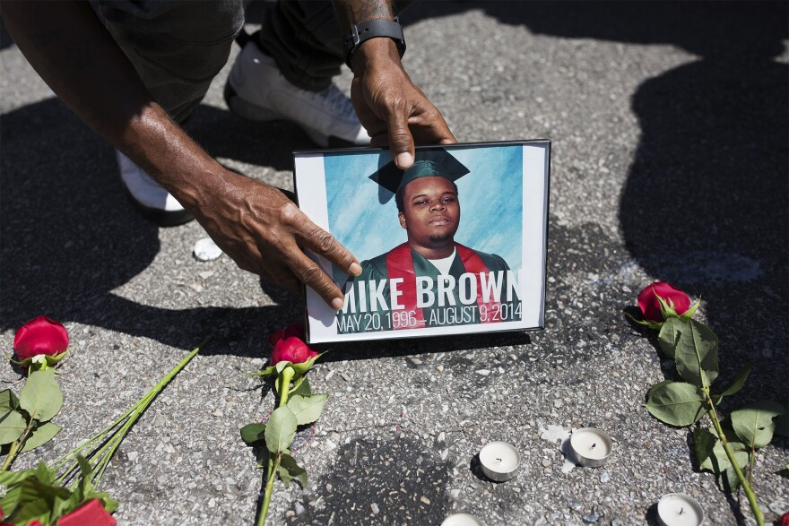 Mourners set roses, candles and photos on the spot where Michael Brown was killed during a memorial event to commemorate the third anniversary.