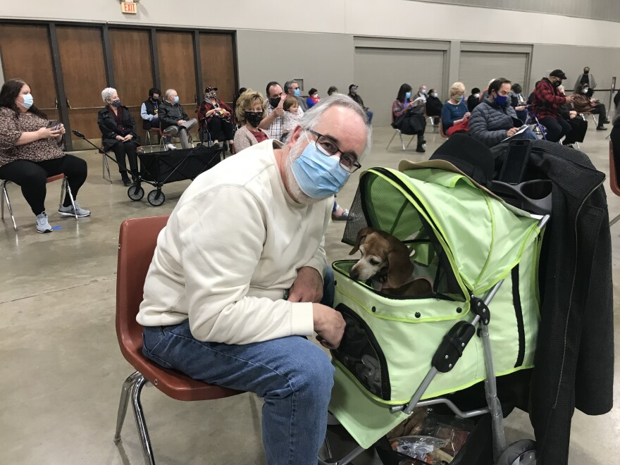 A masked man sits in a chair on a big convention center floor. His dog Zoey, who looks like a dachsund, sits in a green stroller beside him, eyeing some treats.