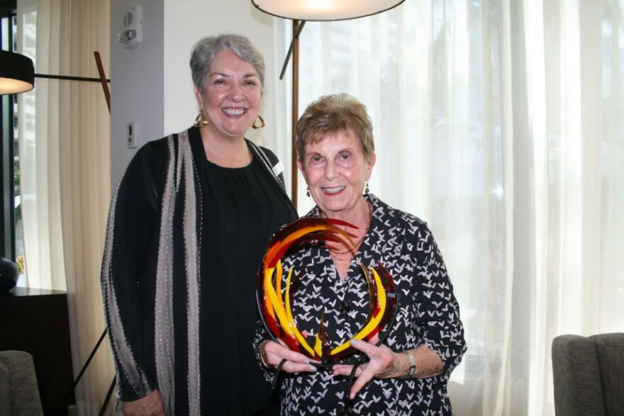 Nancy Roucher holding Dr. Mary Palmer Trailblazer Award  presented by Leiland Theriot