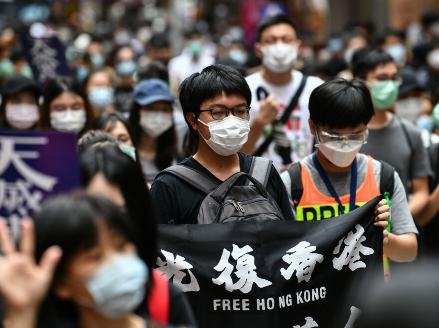 Protesters march on a road during a pro-democracy rally against a proposed new security law in Hong Kong on Sunday. The proposed legislation is expected to ban treason, subversion and sedition, and follows repeated warnings from Beijing that it will no longer tolerate dissent in Hong Kong, which was shaken by months of massive, sometimes violent anti-government protests last year.