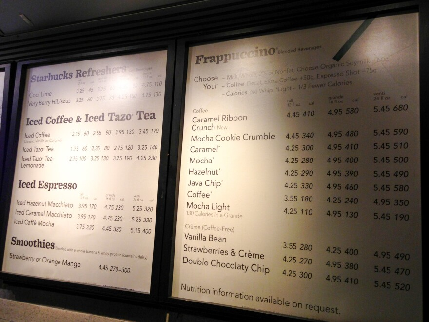 A menu board shows calorie counts hangs at a Starbucks in New York City. The FDA had previously halted the roll out of rules requiring chain restaurants and other food establishments to post calories on menus. Now, the agency says the rules will be in place by May 2018.