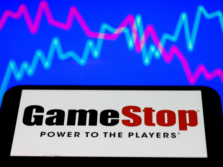 GameStop's logo is displayed on a phone screen, along with an illustrative stock chart on the background, in this illustration photo taken in Poland on Jan. 28. Shares of GameStop have surged as part of a battle between amateur investors and hedge funds.