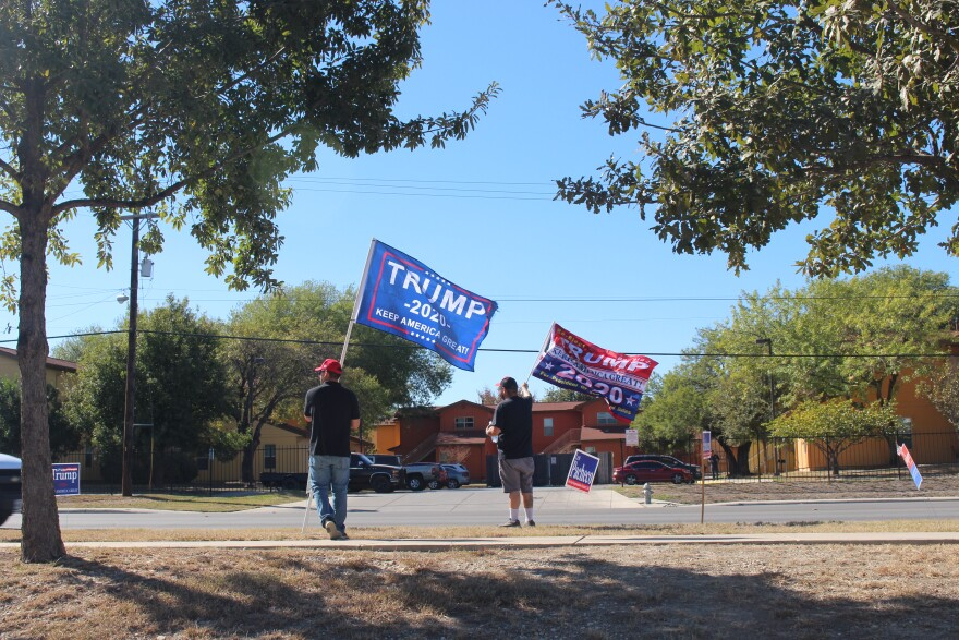 Two Trump supporters join a group of other supporters outside a polling place in Bexar County on Election Day.