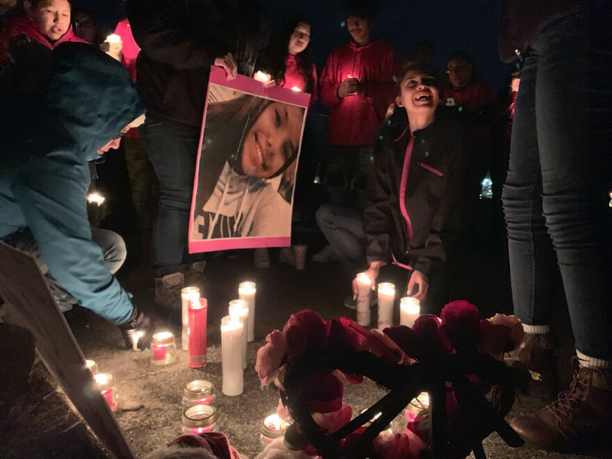 People gather around candles and a picture of Selena Not Afraid at a nighttime vigil.