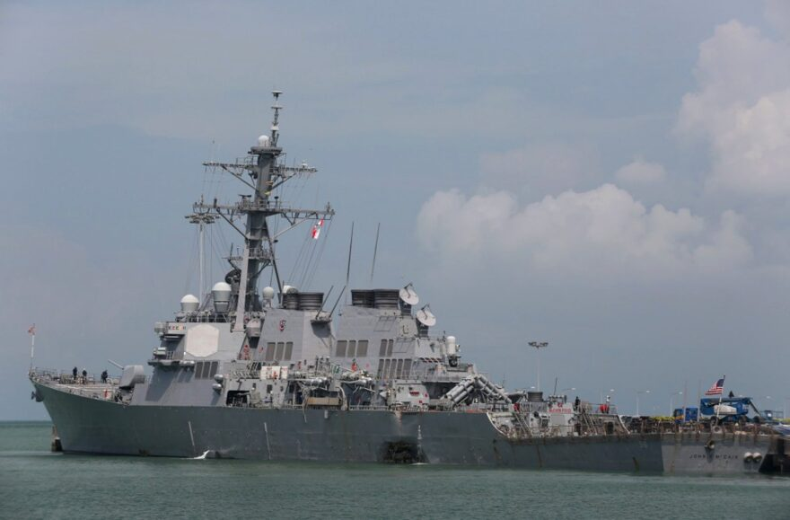 """The guided-missile destroyer USS John S. McCain (DDG 56) is moored pier side at Changi naval base in Singapore following a collision with the merchant vessel Alnic MC Monday, Aug. 21, 2017. The USS John S. McCain was docked at Singapore's naval base with """"significant damage"""" to its hull after an early morning collision with the Alnic MC as vessels from several nations searched Monday for missing U.S. sailors. (Grady T. Fontana/U.S. Navy photo via AP)"""