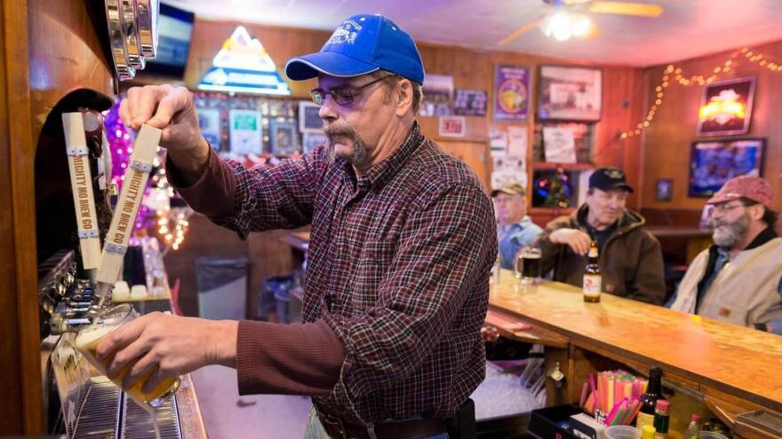 Tracey Somerfeld at Les' Bar drafts a pint of local craft beer. He still farms barley when he's not helping his son run the bar.