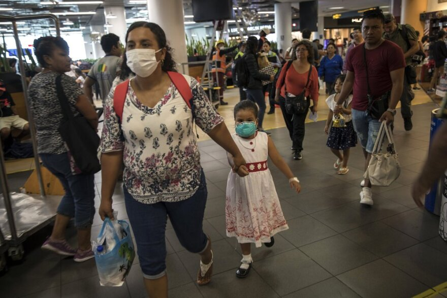 A woman and her daughter walk through Lima's international airport wearing surgical masks this month after Peru reported its first coronavirus case.