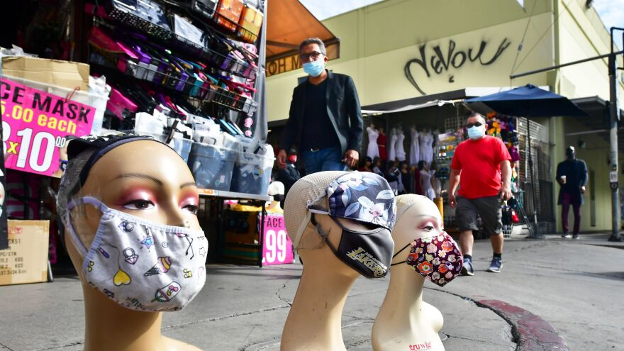 Pedestrians wearing facemasks walk past a display of mannequin heads also wearing facemasks earlier this month in Los Angeles.