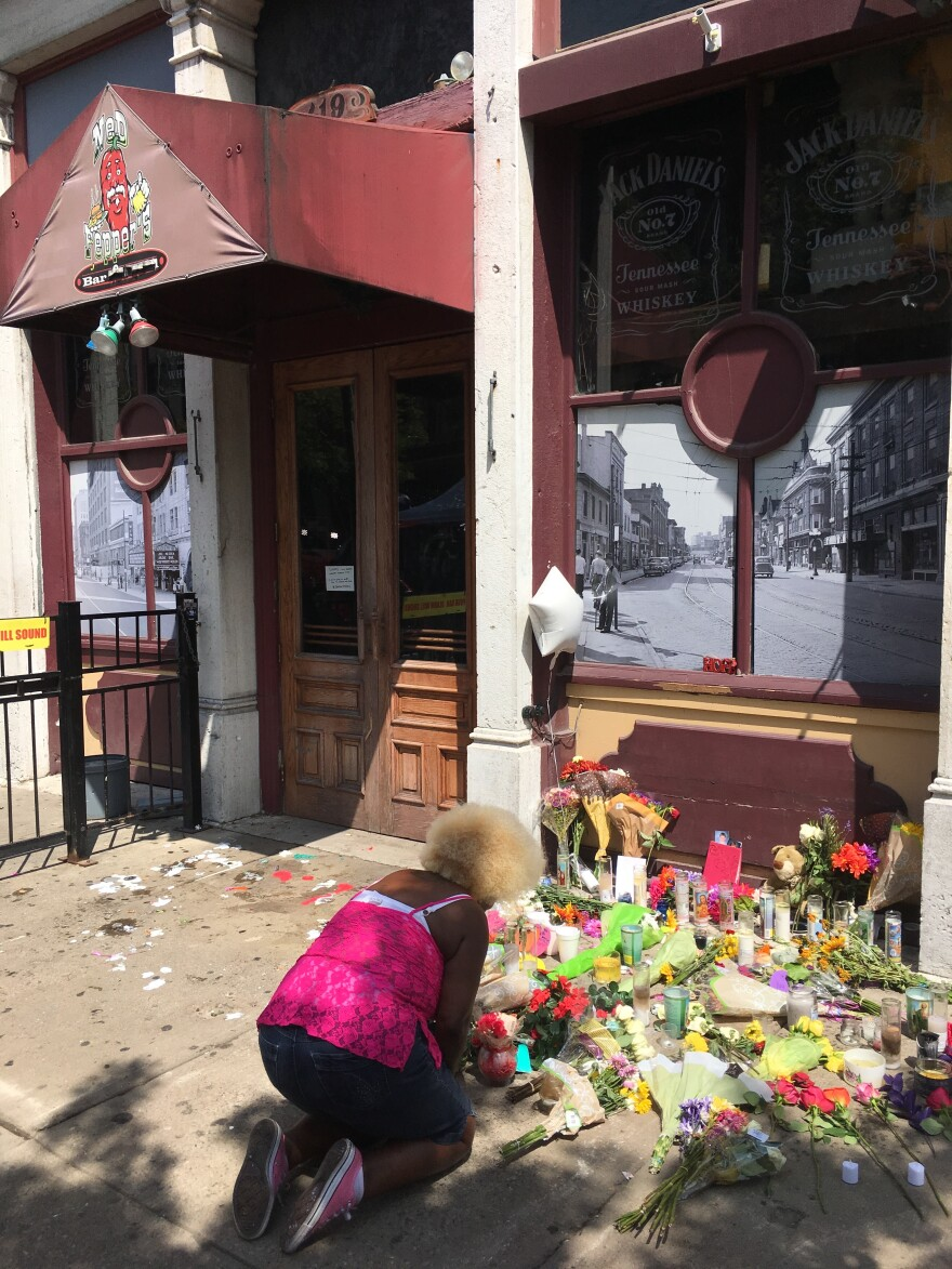 Annette Gibson Strong mourns the loss of friends at the mass shooting memorial in front of Ned Peppers, where 9 people were killed and 27 injured in less than a minute when a gunman opened fire.