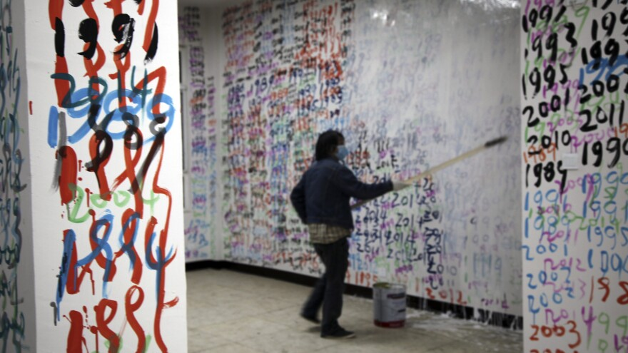 In this April 29, 2014, photo, at a studio in Beijing, China, Chen applies white paint to a wall covered with numbers to represent years, during a performance to commemorate the 25th anniversary of a military crackdown.