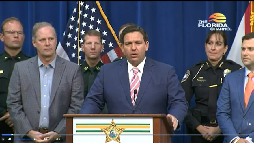Screenshot of man at podium with other men, law enforcement officials, and flags behind him.