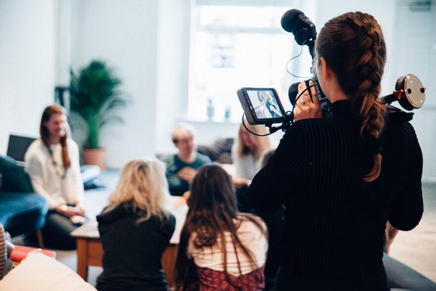 A videographer filming a woman addressing a group of people. Journalists are protecting themselves and their subjects by socially distancing themselves while reporting the news.