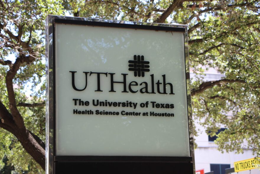 Lighted sign outside UT Health Center in Houston, with tree in the background.
