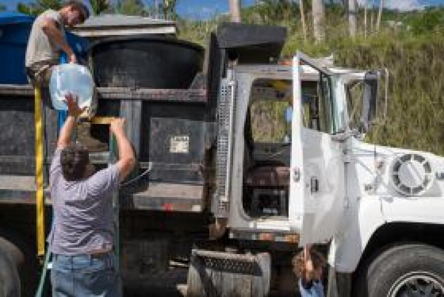 Spec. Wade Scamehorn helps Israel Perez Quiles load clean water unto the back of his dump truck, as Perez Quiles' grandson waits. Perez Quiles makes several runs daily to the location to collect water he then delivers to his neighbors.