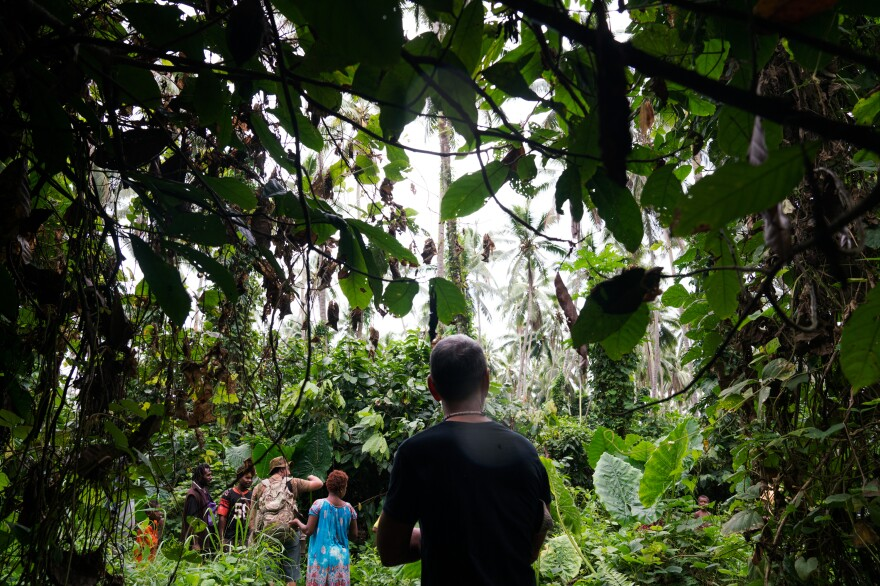 """Jon O'Neill walks through a coconut plantation with a group of local residents. To fill in gaps in his knowledge about his late father's life, he says, """"I have to see what the sky looks like, what the ground looks like, what the people look like."""""""