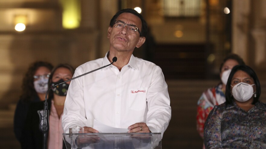 Peru's President Martín Vizcarra speaks in front of the presidential palace after lawmakers voted to remove him from office in Lima, Peru, Monday. Peruvian lawmakers voted overwhelmingly to impeach Vizcarra, expressing anger over his handling of the coronavirus pandemic and citing unproven corruption allegations.