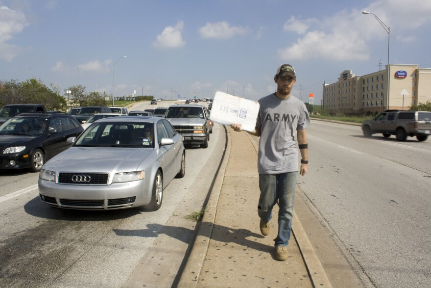 Man in dirty jeans, a t-shirt and ball cap walking along a concrete median holding a cardboard sign out to cars along the road.