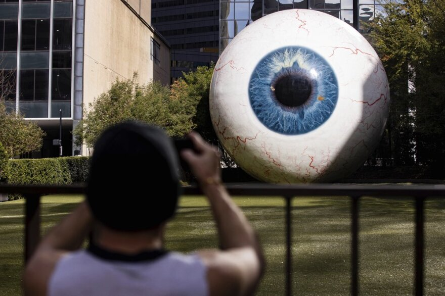 "A person takes a picture of the giant eyeball sculpture ""Eye."" The giant glass eye has a blue iris."