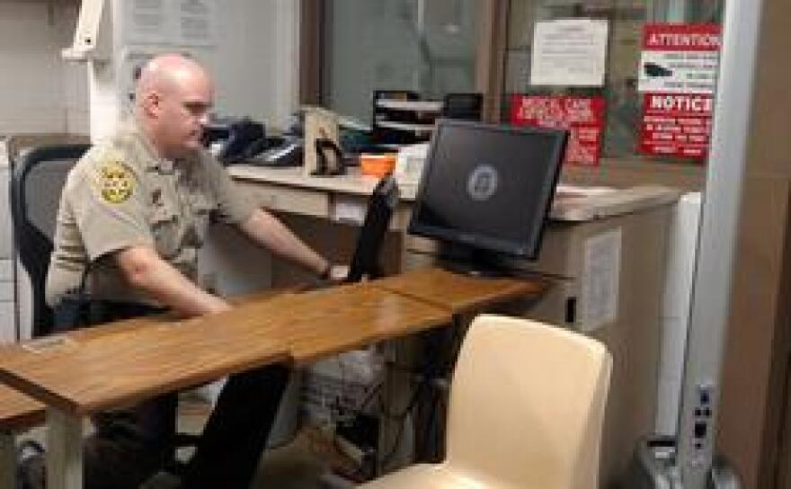 Lieutenant Ryan Snyder sits at a desk in the intake area of the Champaign county jail, where an evidence-based mental health screen is used to flag inmates who may have a serious mental illness.