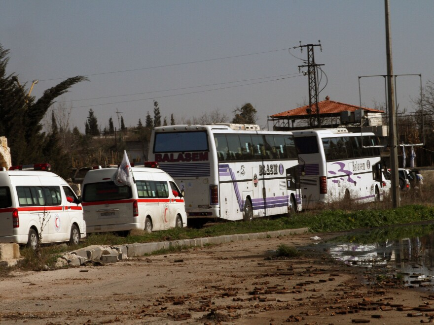 Syrians on two buses followed by the Syrian Arab Red Crescent's vehicles evacuate Syria's battleground city of Homs, on Friday.